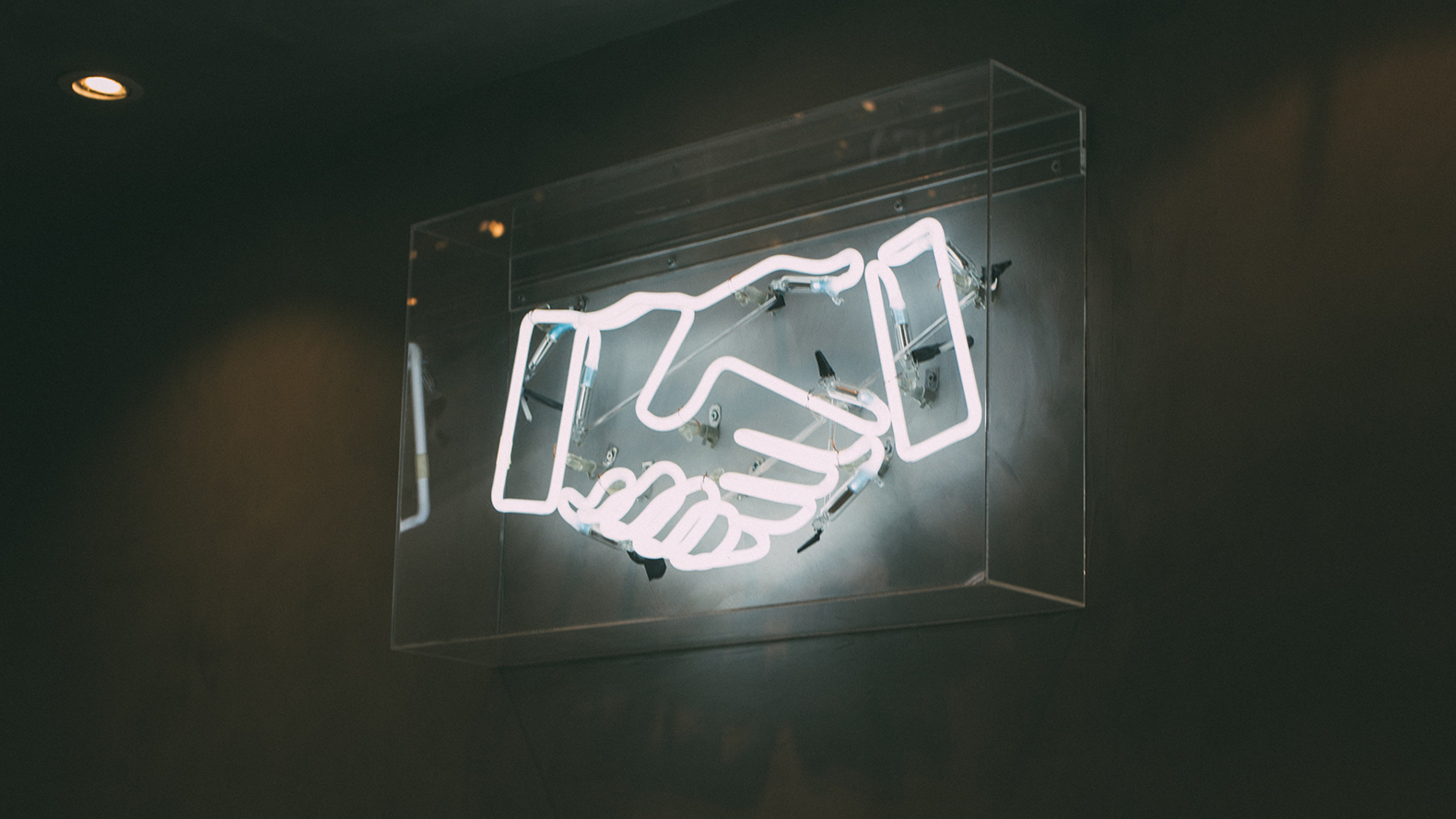 A neon sign of a handshake. Photo by Charles Deluvio on Unsplash