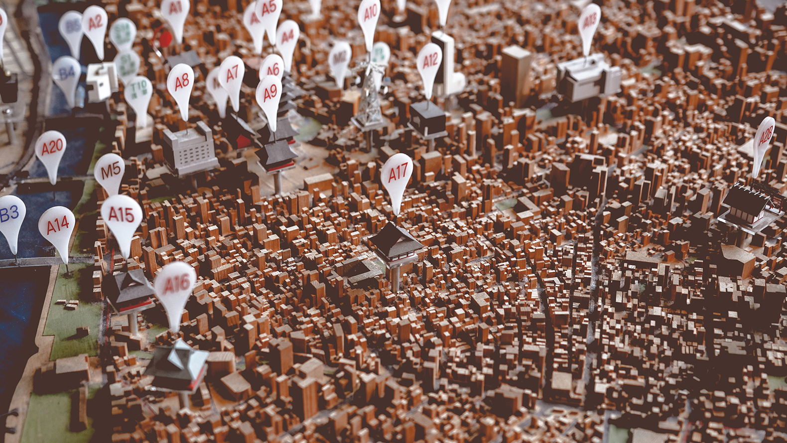 A miniature city with tags over some buildings. Photo: Thor Alvis on Unsplash.