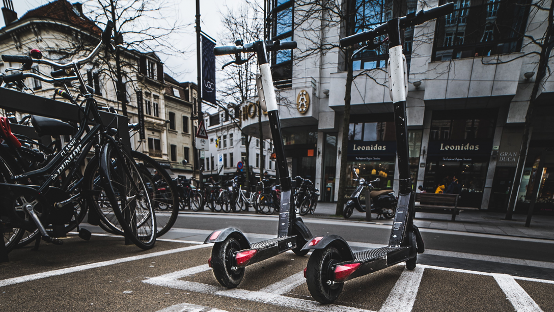E-scooters in a city. Photo by Mika Baumeister on Unsplash.
